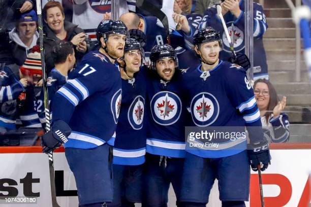 Adam Lowry Brandon Tanev Mathieu Perreault and Jacob Trouba of the Winnipeg Jets celebrate a second period goal against the Tampa Bay Lightning at...