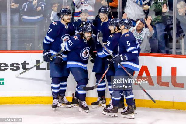 Adam Lowry Mathieu Perreault Tyler Myers Brandon Tanev and Dmitry Kulikov of the Winnipeg Jets celebrate a second period goal against the Vegas...