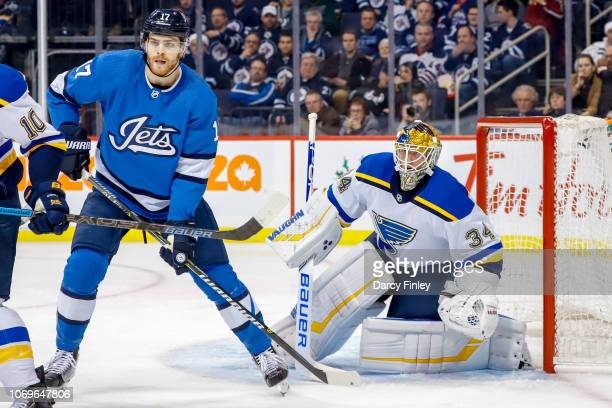 Adam Lowry of the Winnipeg Jets and goaltender Jake Allen of the St Louis Blues keep a eye on the play during third period action at the Bell MTS...