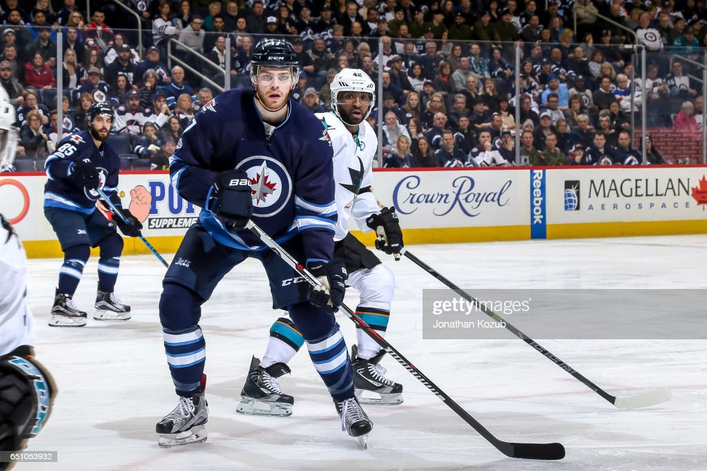 Adam Lowry #17 of the Winnipeg Jets and Joel Ward #42 of the San Jose Sharks keep an eye on the play during second period action at the MTS Centre on March 6, 2017 in Winnipeg, Manitoba, Canada. The Sharks defeated the Jets 3-2.