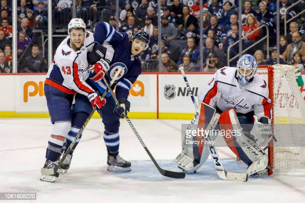 Adam Lowry of the Winnipeg Jets battles for position against Tom Wilson of the Washington Capitals in front of goaltender Pheonix Copley as they keep...