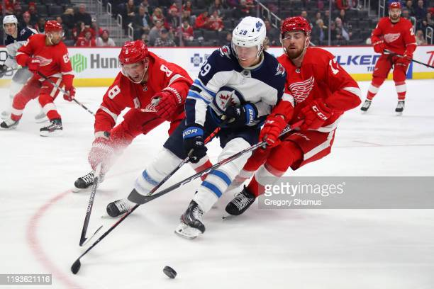 Adam Lowry of the Winnipeg Jets battles for the puck between Justin Abdelkader and Filip Hronek of the Detroit Red Wings during the first period at...