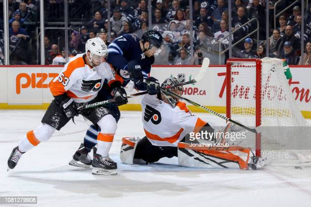Adam Lowry of the Winnipeg Jets breaks in between Shayne Gostisbehere and goaltender Anthony Stolarz of the Philadelphia Flyers to reach the loose...