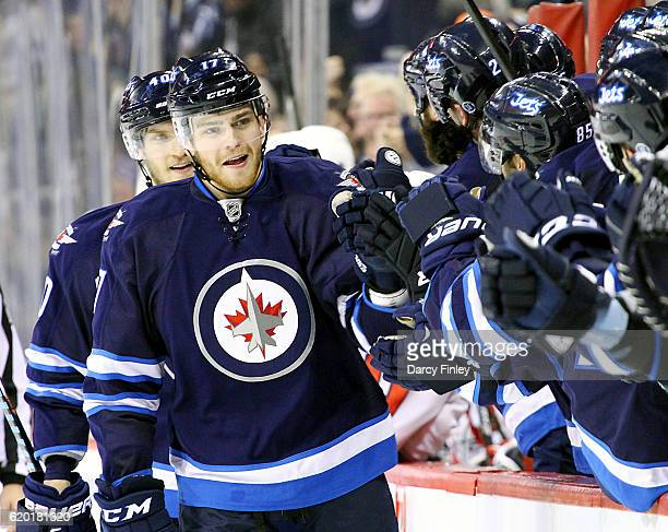 Adam Lowry of the Winnipeg Jets celebrates a third period goal against the Washington Capitals with teammates at the bench at the MTS Centre on...