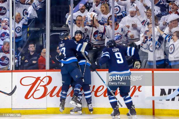 Adam Lowry of the Winnipeg Jets celebrates his first period goal against the St Louis Blues with teammates Brandon Tanev and Andrew Copp in Game Five...