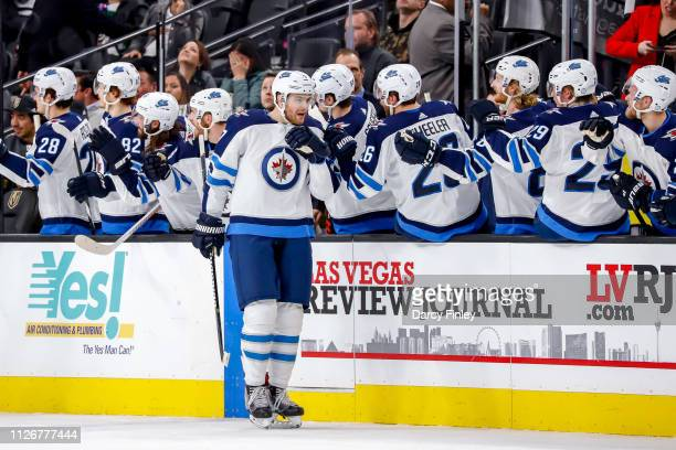 Adam Lowry of the Winnipeg Jets celebrates his second period goal against the Vegas Golden Knights with teammates at the bench at TMobile Arena on...