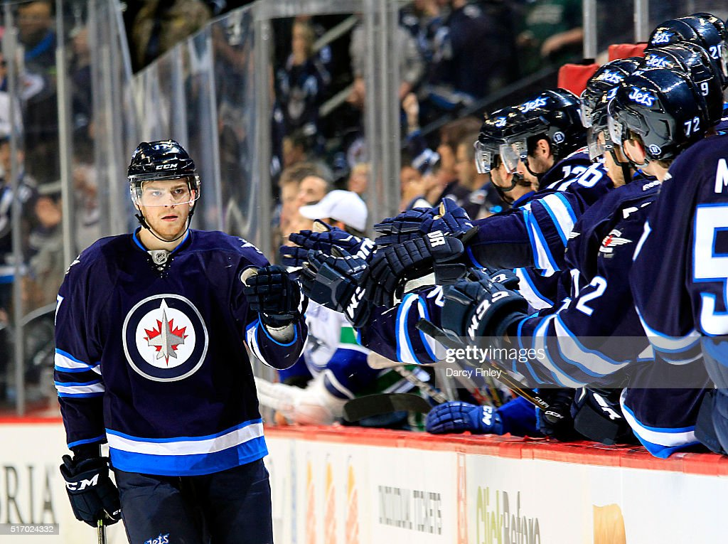 Adam Lowry #17 of the Winnipeg Jets celebrates his third period goal against the Vancouver Canucks with teammates at the bench at the MTS Centre on March 22, 2016 in Winnipeg, Manitoba, Canada.