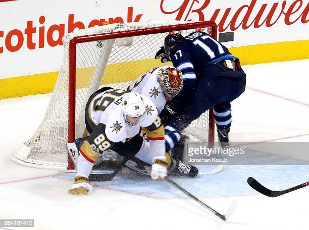 Adam Lowry of the Winnipeg Jets crashes into goaltender Maxime Lagace of the Vegas Golden Knights after driving the net during third period action at...