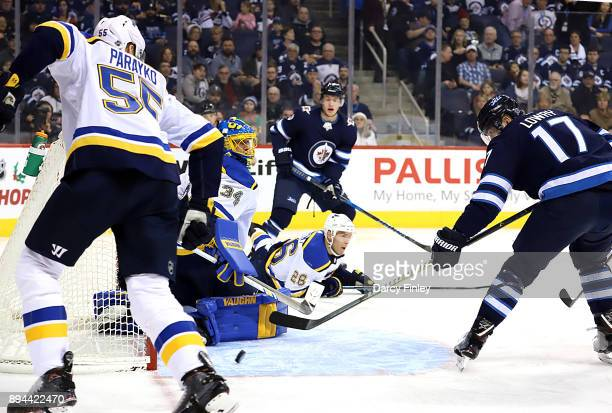 Adam Lowry of the Winnipeg Jets deflects the puck towards the goal past goaltender Jake Allen of the St Louis Blues during second period action at...
