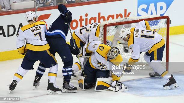 Adam Lowry of the Winnipeg Jets digs for the puck in the pad of Pekka Rinne of the Nashville Predators in Game Four of the Western Conference Second...