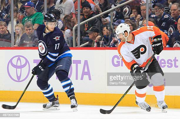 Adam Lowry of the Winnipeg Jets eyes the puck loose in the skates of Radko Gudas of the Philadelphia Flyers during thirdperiod action at the MTS...