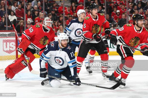 Adam Lowry of the Winnipeg Jets falls in front of goalie Collin Delia of the Chicago Blackhawks in the first period at the United Center on March 29...
