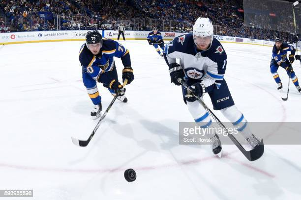 Adam Lowry of the Winnipeg Jets flips the puck as Oskar Sundqvist of the St Louis Blues pressures at Scottrade Center on December 16 2017 in St Louis...