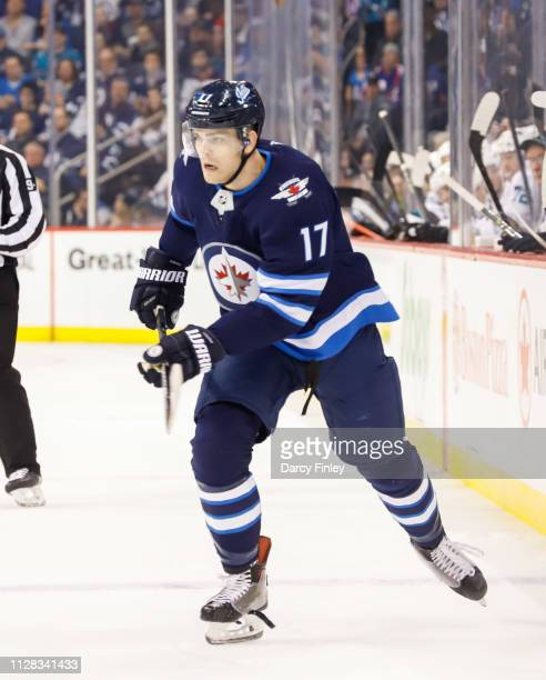 Adam Lowry of the Winnipeg Jets follows the play down the ice during second period action against the San Jose Sharks at the Bell MTS Place on...