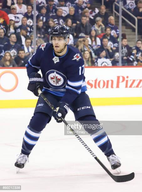Adam Lowry of the Winnipeg Jets keeps an eye on the play during second period action against the Vancouver Canucks at the Bell MTS Place on December...