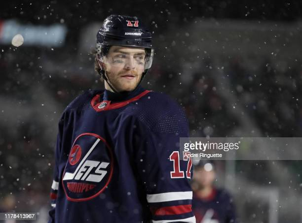 Adam Lowry of the Winnipeg Jets looks on during a stoppage in play against the Calgary Flames during the 2019 Tim Hortons NHL Heritage Classic at...