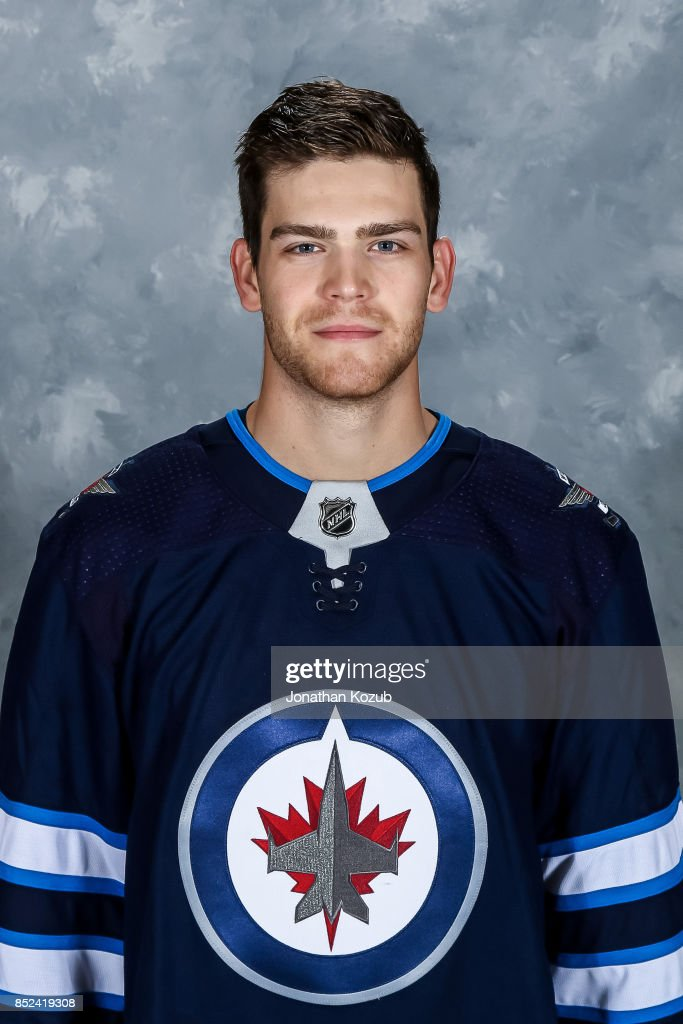 Adam Lowry of the Winnipeg Jets poses for his official headshot for the 2017-2018 season on September 14, 2017 at the Bell MTS Iceplex in Winnipeg, Manitoba, Canada.