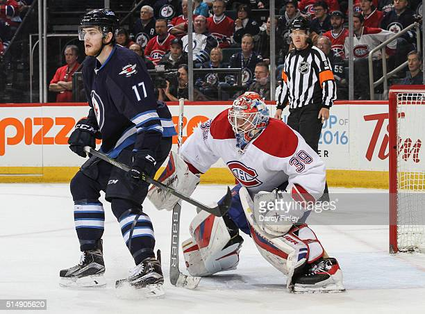 Adam Lowry of the Winnipeg Jets sets a screen in front of goaltender Mike Condon of the Montreal Canadiens as they keep an eye on the play during...