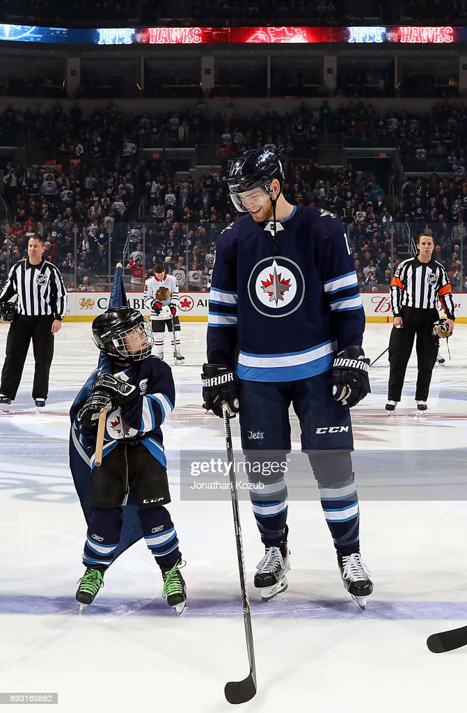 Adam Lowry #17 of the Winnipeg Jets shares a smile with the ScotiaBank skater prior to puck drop against the Chicago Blackhawks at the Bell MTS Place on December 14, 2017 in Winnipeg, Manitoba, Canada.