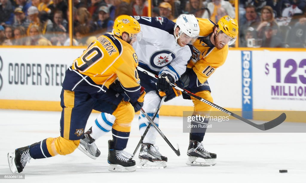 Adam Lowry #17 of the Winnipeg Jets skates against James Neal #18 and Calle Jarnkrok #19 of the Nashville Predators during an NHL game at Bridgestone Arena on March 13, 2017 in Nashville, Tennessee.