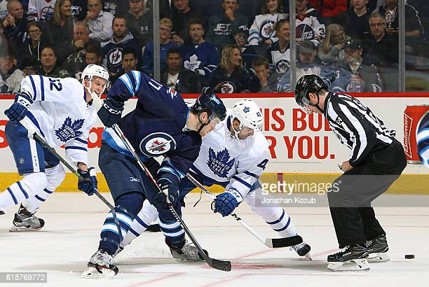 Adam Lowry of the Winnipeg Jets takes a third period faceoff against Nazem Kadri of the Toronto Maple Leafs at the MTS Centre on October 19 2016 in...