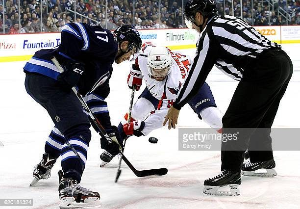 Adam Lowry of the Winnipeg Jets takes a third period faceoff against the Evgeny Kuznetsov of the Washington Capitals at the MTS Centre on November 1...