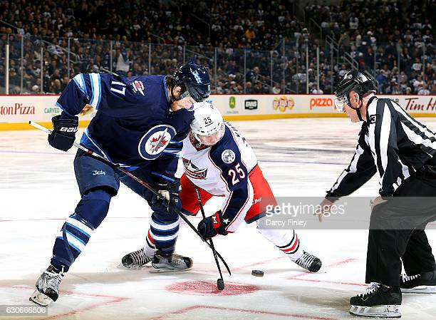 Adam Lowry of the Winnipeg Jets takes a third period faceoff against the William Karlsson of the Columbus Blue Jackets at the MTS Centre on December...