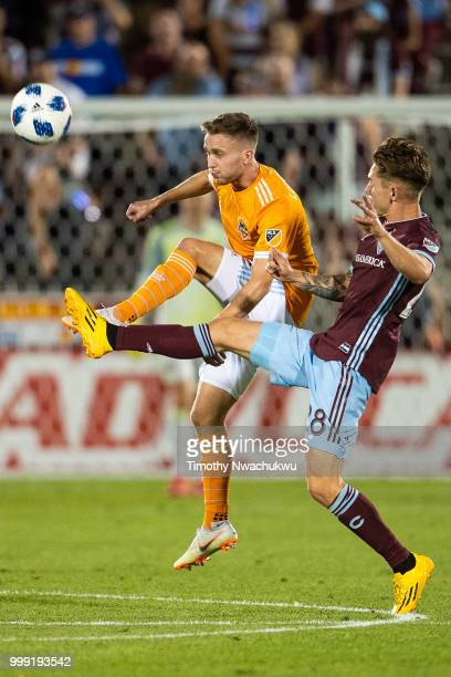 Adam Lundqvist of Houston Dynamo and Sam Nicholson of Colorado Rapids reach for a volley at Dick's Sporting Goods Park on July 14, 2018 in Commerce...