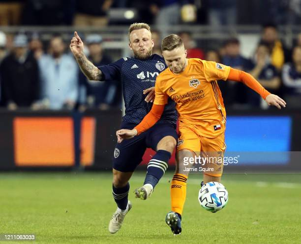 Adam Lundqvist of Houston Dynamo battles Johnny Russell of Sporting Kansas City for the ball during the game at Children's Mercy Park on March 07...