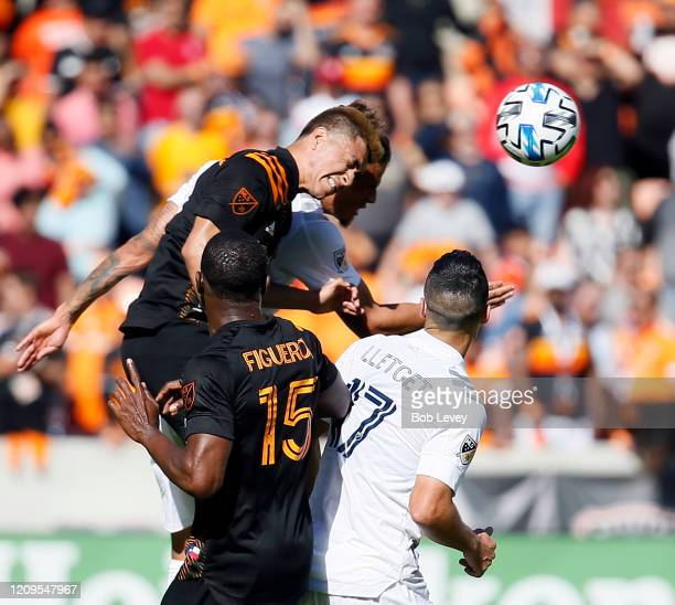Adam Lundqvist of Houston Dynamo heads the ball away from Sebastian Lletget of Los Angeles Galaxy as Maynor Figueroa looks on during the first half...