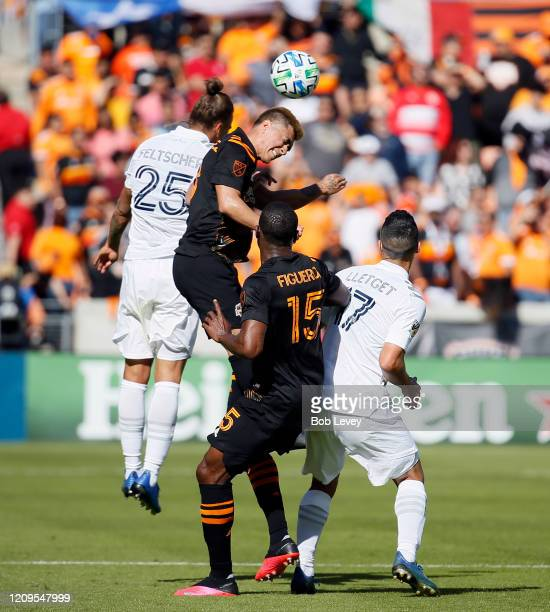 Adam Lundqvist of Houston Dynamo heads the ball away from Sebastian Lletget of Los Angeles Galaxy and Rolf Feltscher as Maynor Figueroa looks on...