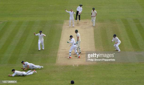 Adam Lyth of England dives to catch the ball parried by Alastair Cook to dismiss Mitchell Starc of Australia off the bowling of Joe Root during the...