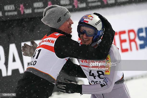 Adam Malysz of Poland is congratulated by teammate Kamil Stoch of Poland after winning the bronze medal in the Men's Ski Jumping HS106 competition...