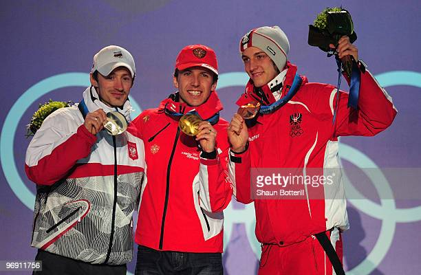 Adam Malysz of Poland receives the silver medal Simon Ammann of Switzerland receives the gold medal and Gregor Schlierenzauer of Austria receives the...