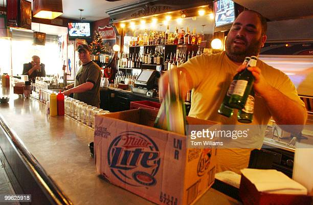 Adam Maradian grabs beer for the cooler at Trusty's bar as Jason Feldman looks on in the establishment located at 1420 Pennsylvania Ave SE Both are...