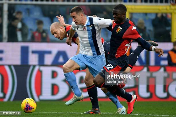 Adam Marusic of SS Lazio competes for the ball with Adama Soumaoro and Andrea Masiello of Genoa CFC during the Serie A match between Genoa CFC and SS...
