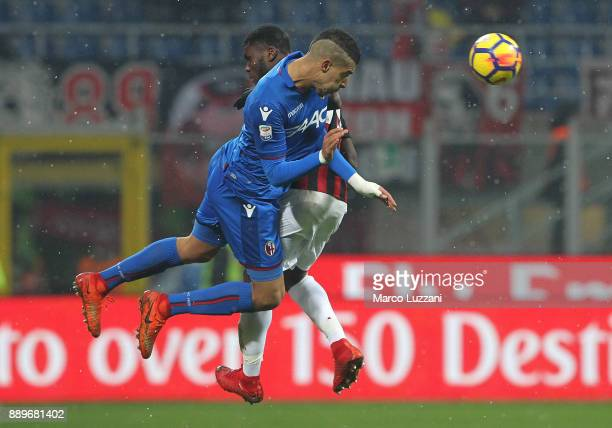Adam Masina of Bologna FC competes for the ball with Franck Kessie of AC Milan during the Serie A match between AC Milan and Bologna FC at Stadio...