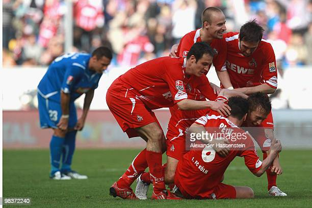 Adam Matuschyk of Koeln celebrates scoring his second team goal with his team mates whilst Sejad Salihovic of Hoffenheim looks dejected during the...
