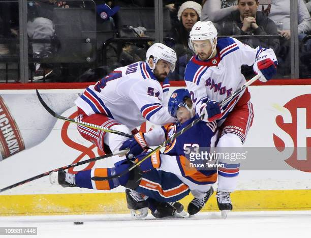 Adam McQuaid and Kevin Shattenkirk of the New York Rangers combine to hit Casey Cizikas of the New York Islanders during the third period at the...