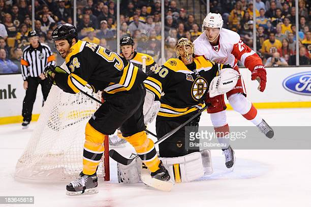 Adam McQuaid and Tuukka Rask of the Boston Bruins fight for the puck against Cory Emmerton of the Detroit Red Wings at the TD Garden on October 5...