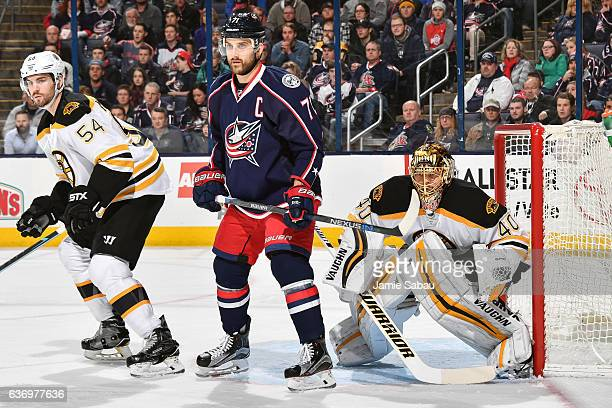 Adam McQuaid of the Boston Bruins and Nick Foligno of the Columbus Blue Jackets skate in front of goaltender Tuukka Rask of the Boston Bruins on...