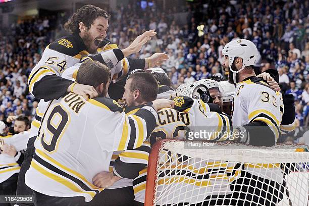 Adam McQuaid of the Boston Bruins celebrates with his teammates Brad Marchand, Tyler Seguin, Tim Thomas and Zdeno Chara after defeating the Vancouver...