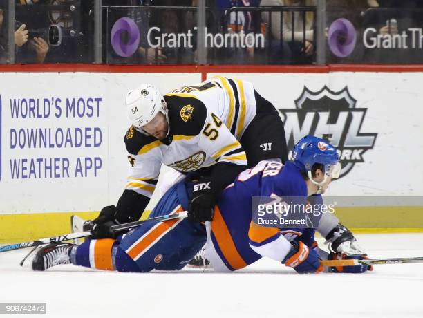 Adam McQuaid of the Boston Bruins checks Anthony Beauvillier of the New York Islanders during the first period at the Barclays Center on January 18...