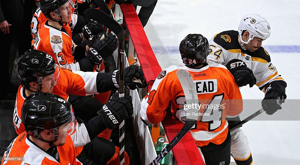 Adam McQuaid #54 of the Boston Bruins checks Matt Read #24 of the Philadelphia Flyers into the boards on November 29, 2016 at the Wells Fargo Center in Philadelphia, Pennsylvania. The Flyers went on to defeat the Bruins 3-2 in a shootout.