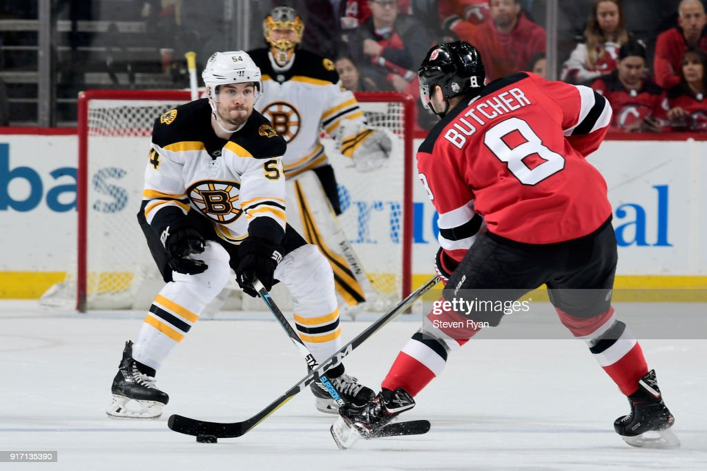 Adam McQuaid #54 of the Boston Bruins defends Will Butcher #8 of the New Jersey Devils during the third period at Prudential Center on February 11, 2018 in Newark, New Jersey. The Boston Bruins defeated the New Jersey Devils 5-3.