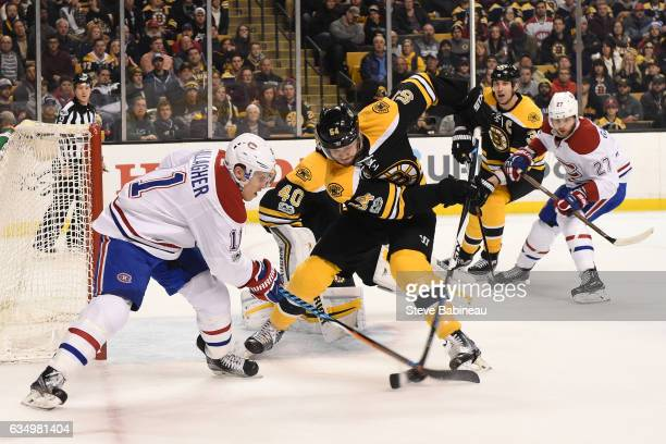 Adam McQuaid of the Boston Bruins fights for the puck against Brendan Gallagher of the Montreal Canadiens at the TD Garden on February 12 2017 in...