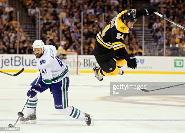 Adam McQuaid of the Boston Bruins flys through the air after being checked by Andrew Alberts of the Vancouver Canucks during Game Three of the 2011...