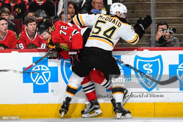 Adam McQuaid of the Boston Bruins hits Artemi Panarin of the Chicago Blackhawks in the first period at the United Center on April 2 2017 in Chicago...