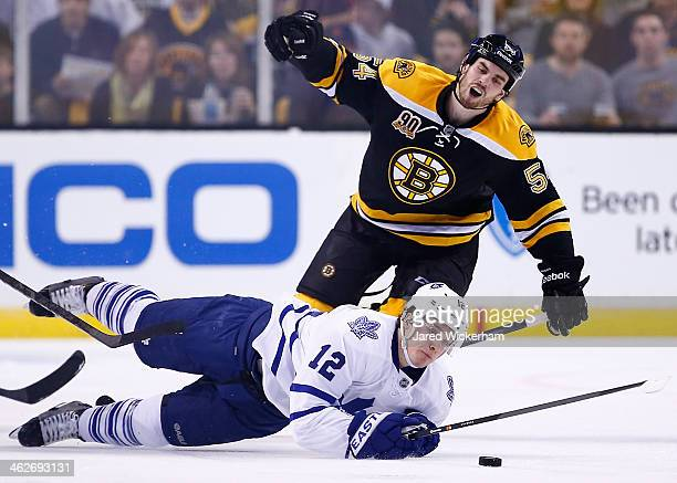 Adam McQuaid of the Boston Bruins is called for a tripping penalty on Mason Raymond of the Toronto Maple Leafs in the second period during the game...