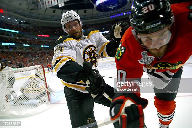 Adam McQuaid of the Boston Bruins pushes Brandon Saad of the Chicago Blackhawks into the boards in Game Two of the NHL 2013 Stanley Cup Final at...